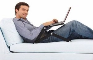 un homme qui utilise un ordinateur sur un lit grâce à cette tablette ajustable